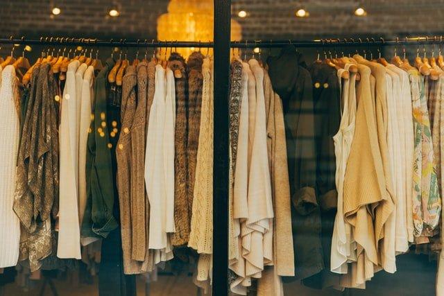 Beautiful stylish fashion clothing items hanging on a rack